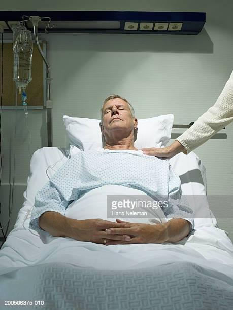 Senior woman by senior man lying asleep in hospital bed