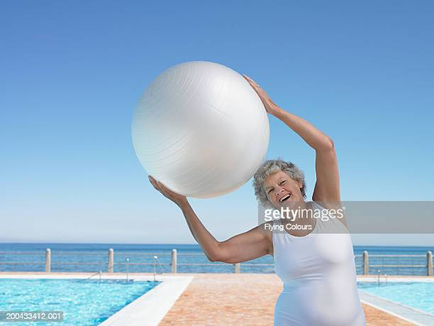 senior woman by swimming pool using exercise ball, smiling, portrait - alte frau badeanzug stock-fotos und bilder