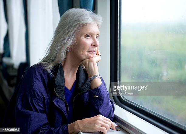 Senior woman by window on train