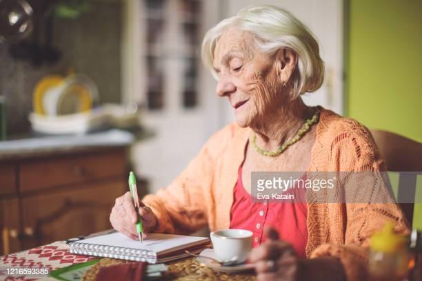 hogere vrouw die financiën in haar keuken berekent - 80 89 jaar stockfoto's en -beelden