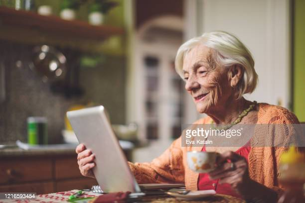 senior woman calculating finances in her kitchen - 70 79 years stock pictures, royalty-free photos & images