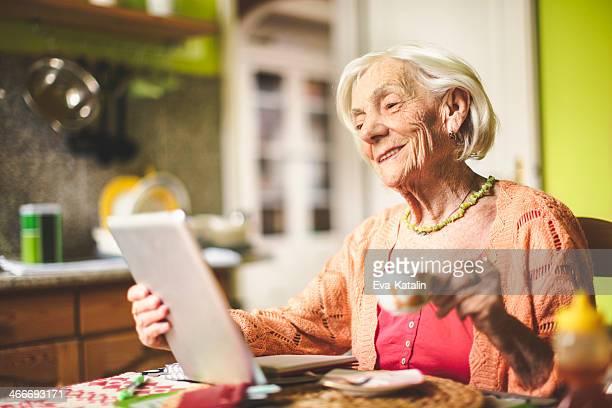 Senior Frau Berechnung Finanzen in Ihrer Küche