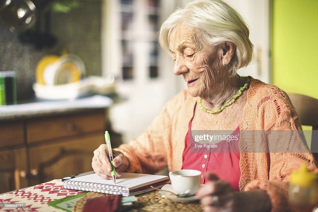 Senior woman calculating finances in her kitchen : Stock Photo