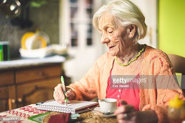 Senior woman calculating finances in her kitchen