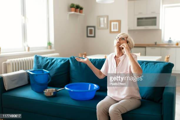 senior woman calling plumber for water leakage at home - leaking stock pictures, royalty-free photos & images