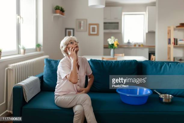 senior woman calling plumber for water leakage at home - damaged stock pictures, royalty-free photos & images