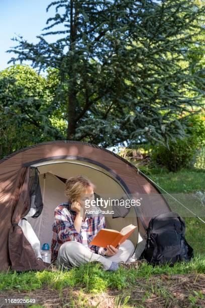 senior vrouw kamperen en het lezen van een boek in het bos - slovenië stockfoto's en -beelden