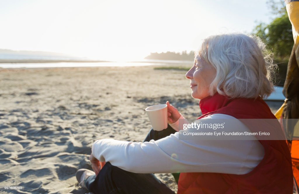 Senior woman camping on beach looking at ocean view : Stock Photo