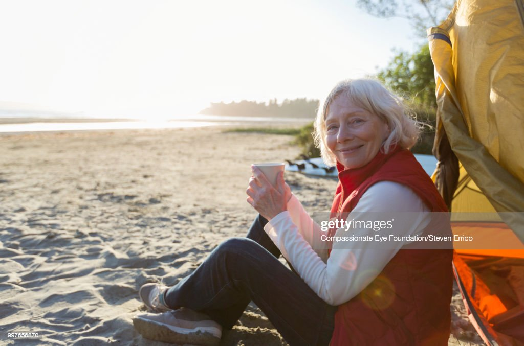 Senior woman camping on beach with coffee : Stock Photo