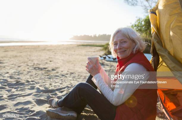 Senior woman camping on beach with coffee