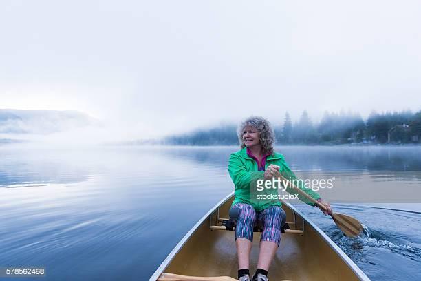 Senior woman canoeing on a prisitine lake