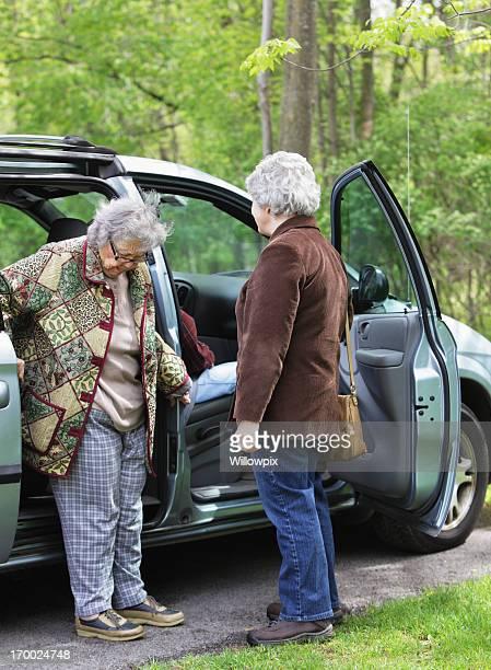Senior Frau sorgfältig Eingabe Minivan Auto