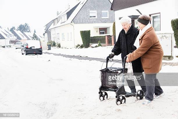 senior woman caregiver and walker on snow road