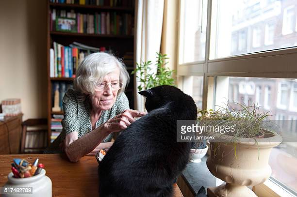 Senior woman caressing her cat