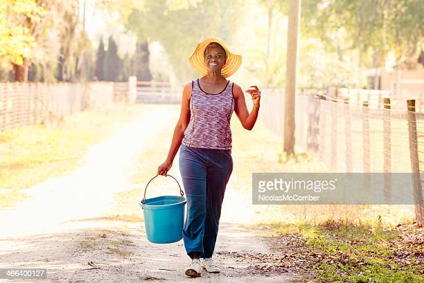 Senior woman carrying a bucket