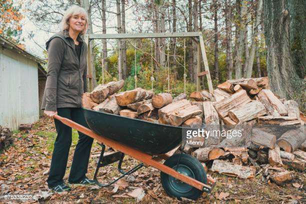 senior woman carrying firewood with wheelbarrow in autumn - wheelbarrow stock photos and pictures