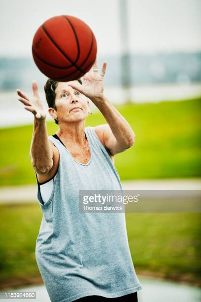 Senior woman catching pass during early morning basketball game