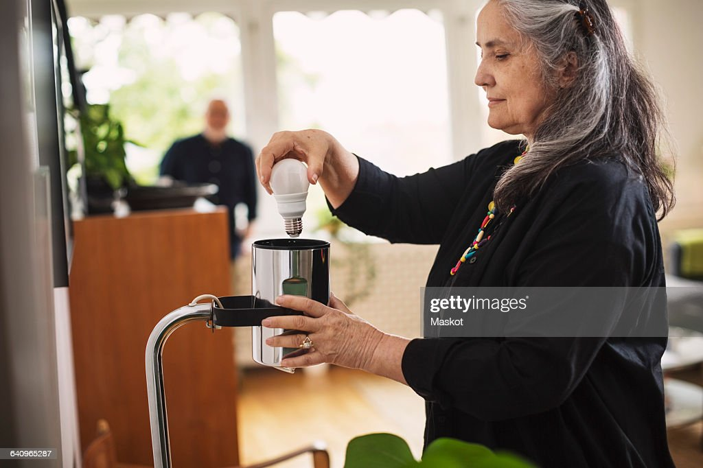 Senior woman changing bulb at home : Stock Photo