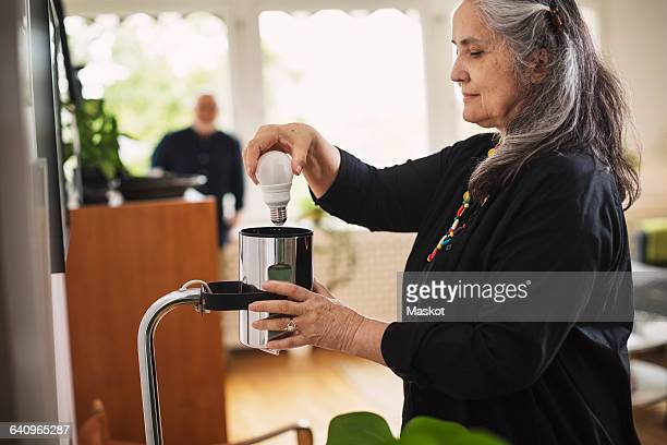 Senior woman changing bulb at home