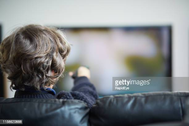 senior woman changing channels on her tv set with remote control - television show stock pictures, royalty-free photos & images