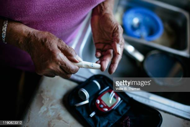 senior woman checking blood sugar levels - diabetes stock pictures, royalty-free photos & images