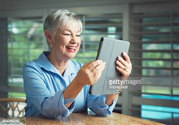 senior woman checking digital tablet - grandma invoice stock pictures, royalty-free photos & images