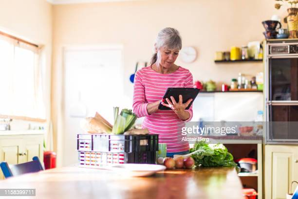 senior woman checking her fresh vegetable delivery - grocery delivery stock pictures, royalty-free photos & images