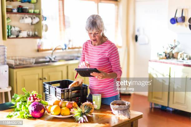 Senior woman checking her fresh vegetable delivery
