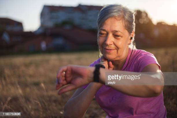 senior woman checking her pulse after exercise - cardiovascular system stock pictures, royalty-free photos & images