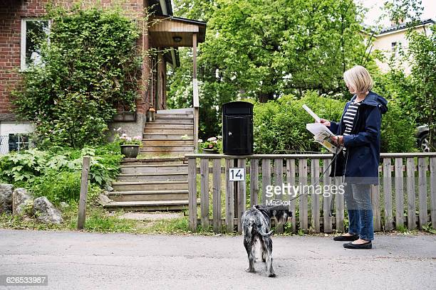 Senior woman checking letters while standing with dog outside house