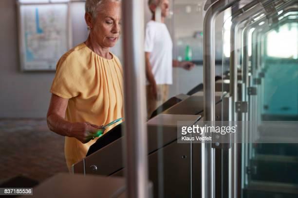 Senior woman checking out at metro station