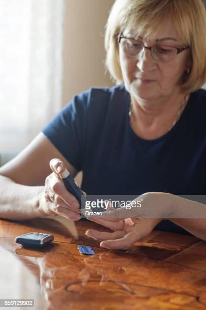 Ältere Frau, die Kontrolle der Blutzuckerwerte