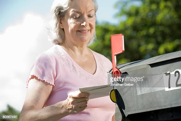 a senior woman checking the mailbox - domestic mailbox stock pictures, royalty-free photos & images