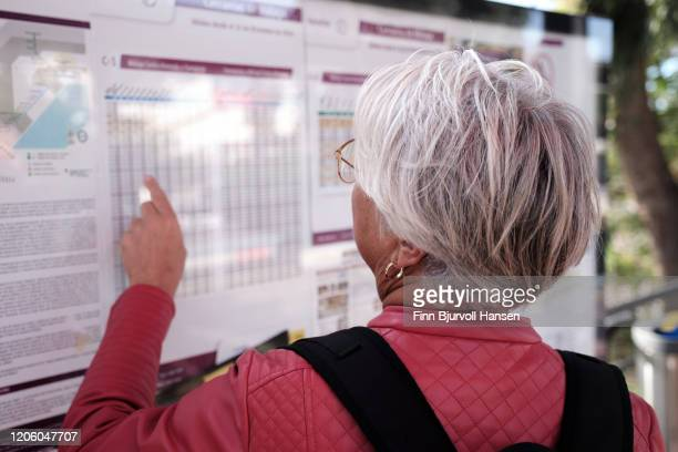 senior woman checking time table at railwaystation - finn bjurvoll - fotografias e filmes do acervo