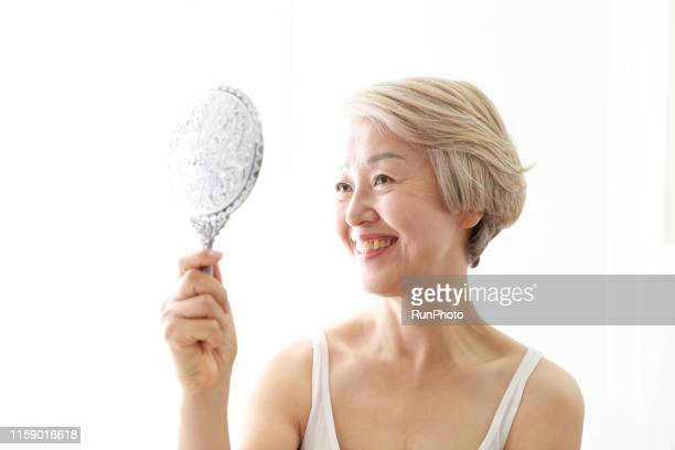 senior woman checking wrinkled face in mirror - 人の肌 ストックフォトと画像