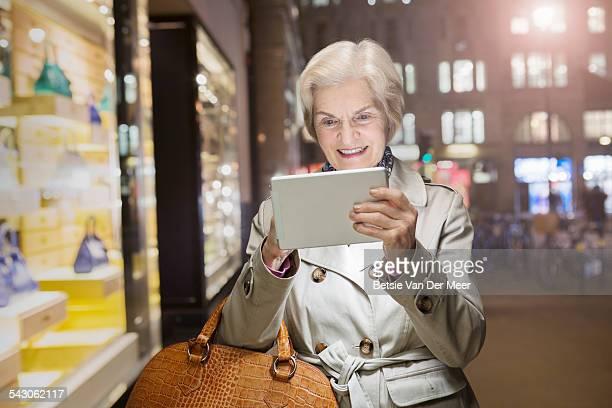 Senior woman checks digital tablet in street.