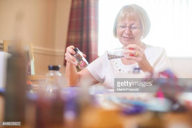 Senior woman choosing decoration for greeting card