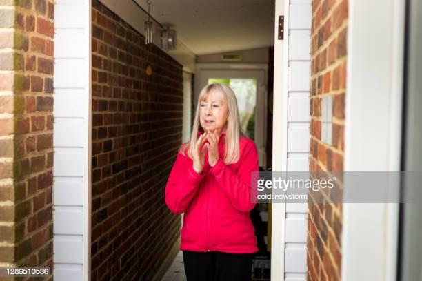 senior woman clapping hands at home during covid-19 pandemic - state of emergency stock pictures, royalty-free photos & images