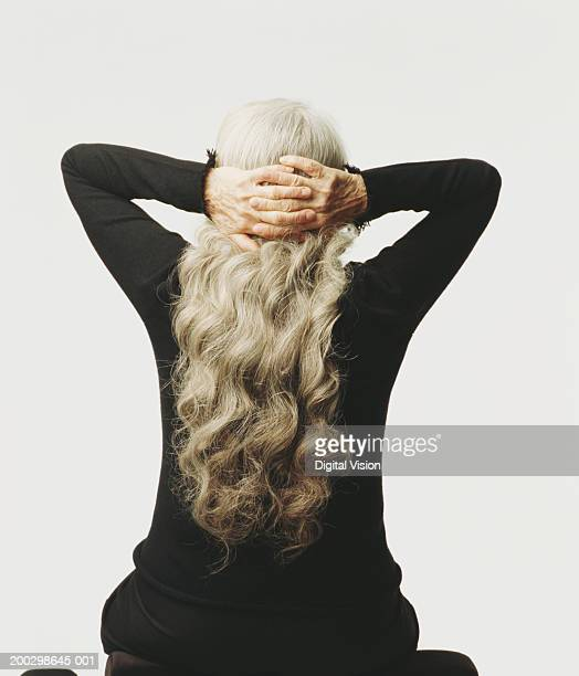 Senior woman clasping hands behind head, rear view
