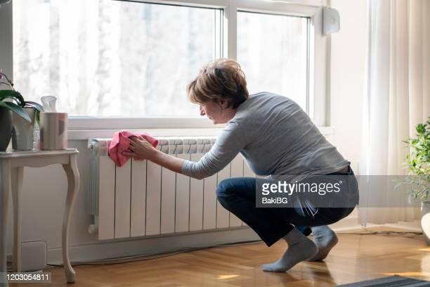 シニア女性クリーニングホーム - 暖房用ラジエーター ストックフォトと画像