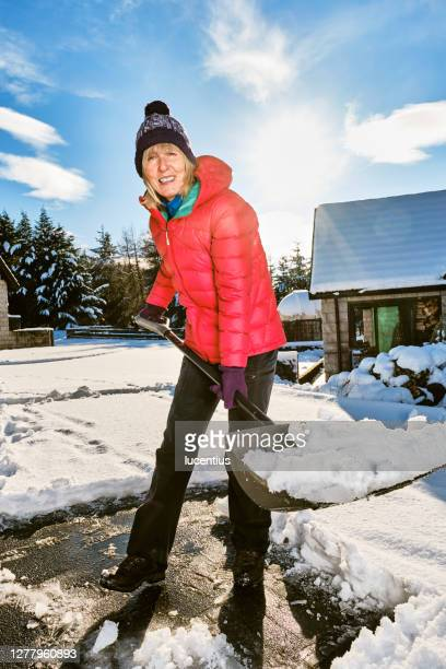 senior woman clearing snow from her front yard using a snow shov - snow shovel stock pictures, royalty-free photos & images