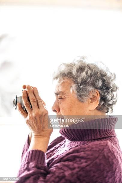 Senior vrouw verzamelen herinneringen door het nemen van de foto