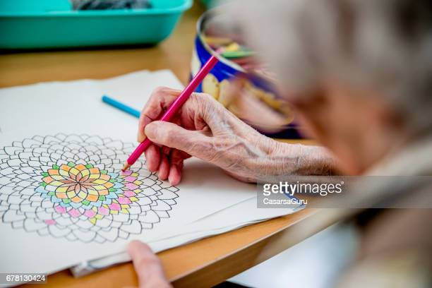 senior woman coloring mandala - colouring stock pictures, royalty-free photos & images