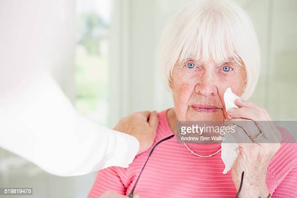 Senior woman consoled by her carer