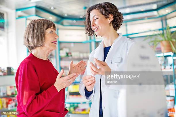 Senior woman consulting medicine dosage with the pharmacist