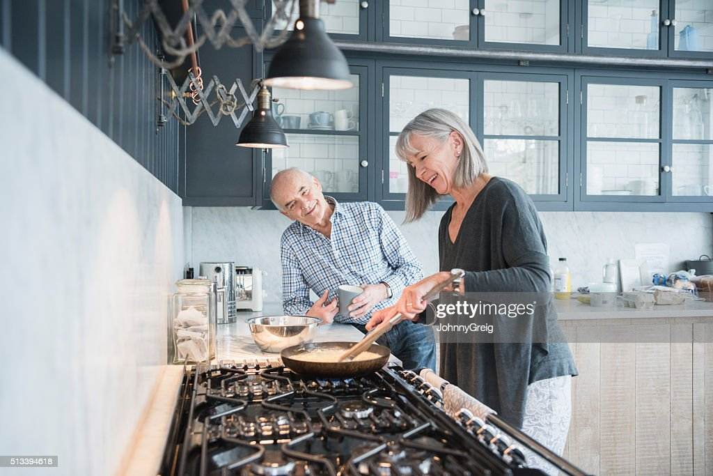 Senior woman cooking dinner talking to her husband : Stock Photo