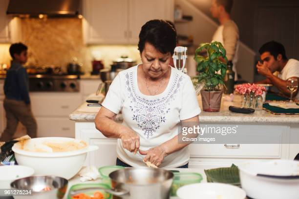 senior woman cooking food while sons and grandson in background at kitchen - grandmother stock pictures, royalty-free photos & images