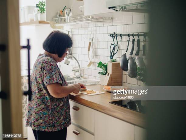 senior woman cooking healthy food in the kitchen - raw food diet stock pictures, royalty-free photos & images