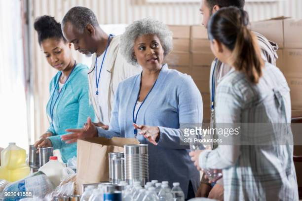 senior woman coordinates food bank volunteers - homeless shelter stock pictures, royalty-free photos & images