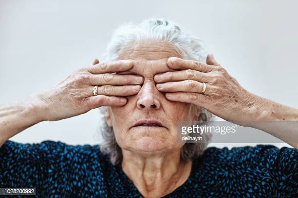 senior woman covering eyes with hands - obscured face stock pictures, royalty-free photos & images